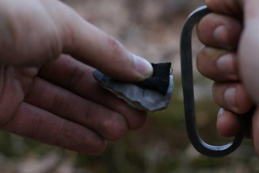 Acciarino in acciaio e frammento di selce su cui è stato posizionato un pezzo di tessuto carbonizzato come esca per le scintille